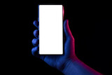 Fototapeta Uliczki - Phone in hand. Silhouette of male hand lit with blue and red neon lights holding bezel-less smartphone on black background. Screen is cut with clipping path.