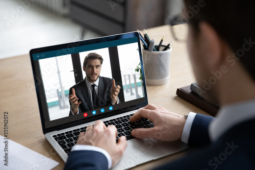 Fotografering Back view of businessman sit at desk have video call on laptop with male busines