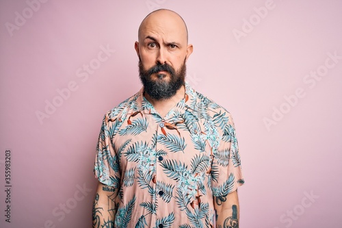 Handsome bald man with beard and tattoo wearing casual floral shirt over pink background skeptic and nervous, frowning upset because of problem Wallpaper Mural