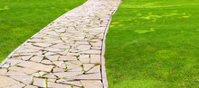 Flagstone Footpath In A Park With A Green Lawn Goes Into Perspective On A Sunny Summer Day, Closeup Of Brown Paving Stone Tiles With Copy Space 16:9.