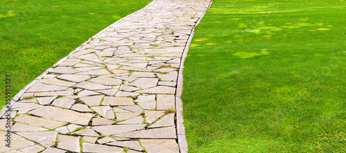 Obraz na płótnie flagstone footpath in a park with a green lawn goes into perspective on a sunny summer day, closeup of brown paving stone tiles with copy space 16:9