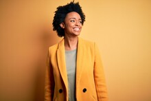 Young Beautiful African American Afro Businesswoman With Curly Hair Wearing Yellow Jacket Looking Away To Side With Smile On Face, Natural Expression. Laughing Confident.