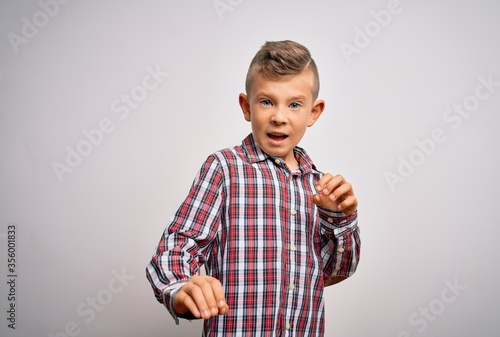 Obraz Young little caucasian kid with blue eyes wearing elegant shirt standing over isolated background disgusted expression, displeased and fearful doing disgust face because aversion reaction. - fototapety do salonu