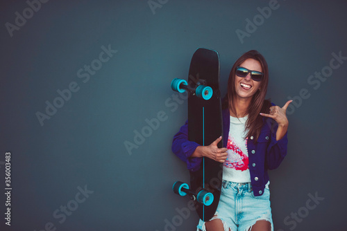 Obraz Young happy girl in sunglasses showing shaka with skateboard in front of grey wall. - fototapety do salonu
