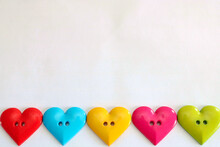 Colourful Heart Shaped Buttons In A Line Along Bottom Of Image. Background Is White Cartridge Paper. LGBT And Equality Image. Love Is Many Colours And Flavours Valentines Day Concept. Copy Space.