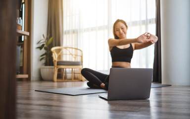 A beautiful young asian woman stretching arms while watching online workout tutorials on laptop at home