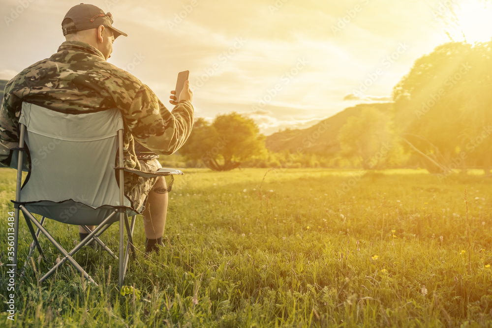 Fototapeta man with smart phone in the mountains