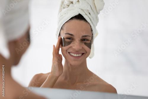 Fototapeta Mirror reflection smiling woman wearing white bath towel on head applying hydrogel eye care patches, standing in bathroom, moisturizing skin under eyes, enjoying skincare procedures obraz na płótnie