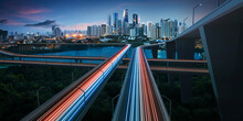 Highway With Vehicle Light Trails Leading To Modern City