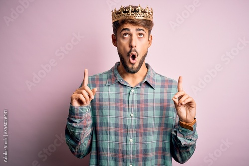 Fototapeta Young man with beard wearing golden crown of king standing over isolated pink background amazed and surprised looking up and pointing with fingers and raised arms. obraz