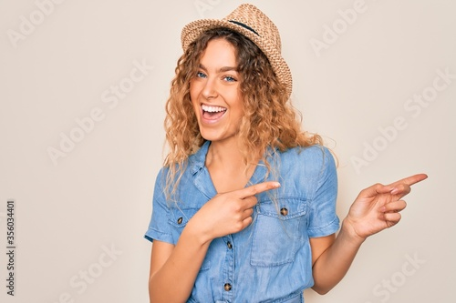 Obraz Young beautiful woman with blue eyes wearing casual denim dress and summer hat smiling and looking at the camera pointing with two hands and fingers to the side. - fototapety do salonu