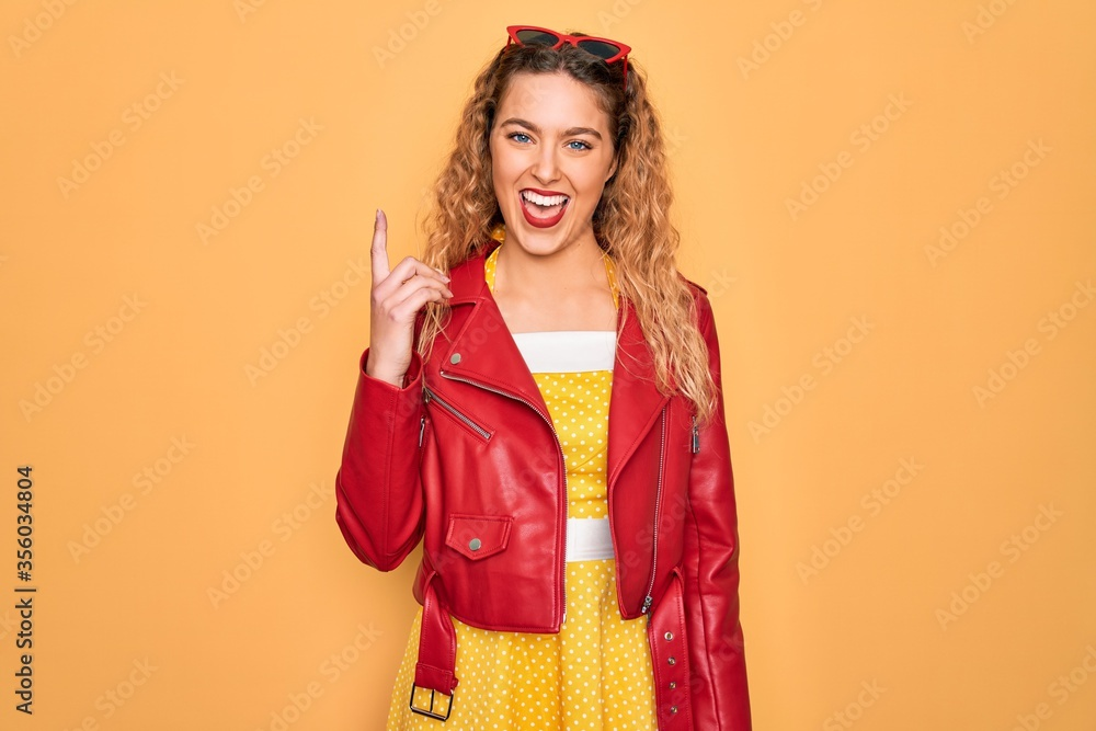 Fototapeta Young beautiful blonde woman pin-up with blue eyes wearing red sunglasses and jacket pointing finger up with successful idea. Exited and happy. Number one.