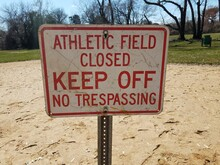 White And Red Athletic Field Closed Keep Off No Trespassing Sign On Dirt
