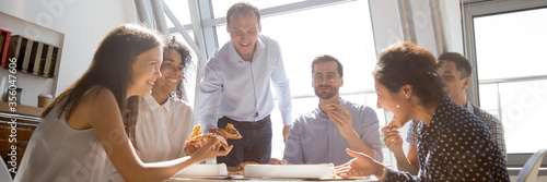 Group of multiethnic colleagues friends gathered together eating pizza talking and laughing during lunch break Fototapete