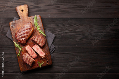 Fototapeta Grilled beef steaks on cutting board obraz