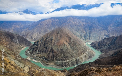 River surrounding mountain with hills and a cloudy sky