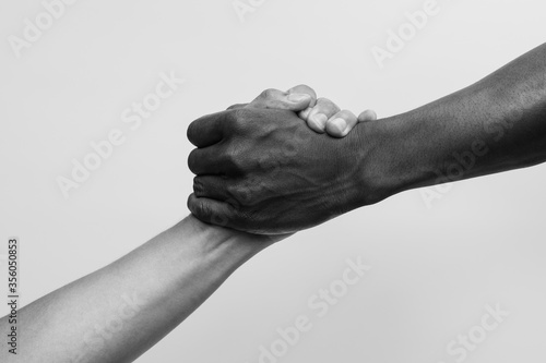 Fotografie, Obraz Helping hand, Rescue, multiathnic people, Black and white image.