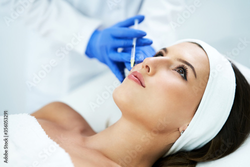 Fototapeta Beautiful young woman getting acid face treatment at beauty salon
