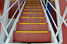 Red Metal Steps Or Stairs With Railing On Ship