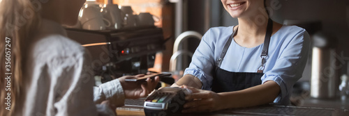 Photo Customer stand near bar counter pay bill using cell application and pos machine