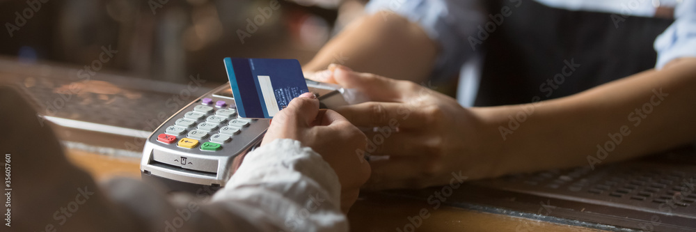 Fototapeta Customer stand near bar counter make payment use contactless credit card close up hands device view, cashless method pay bills in commercial places concept. Horizontal banner for website header design