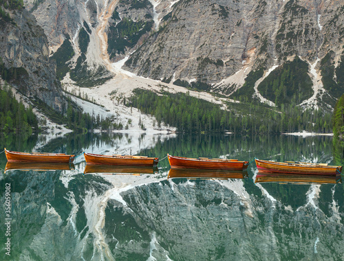 Leinwand Poster wooden boats mirroring in the clear calm water of  Pragser Wildsee (Lago di Brai