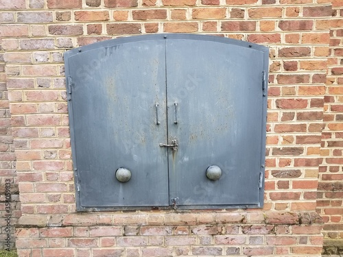 red brick wall and iron metal door