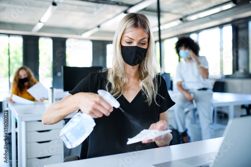 Obraz Young woman with face mask back at work in office after lockdown, disinfecting hands. - fototapety do salonu