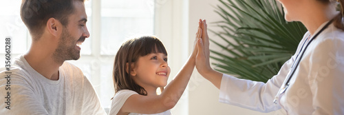 Fototapeta Little daughter gives high five to female doctor, pediatrician greets small kid girl patient, child healthcare medical check up, friendly relation concept