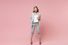 Successful Young African American Business Woman In Grey Suit, White Shirt Posing Isolated On Pink Background In Studio. Achievement Career Wealth Business Concept. Mock Up Copy Space. Looking Camera.