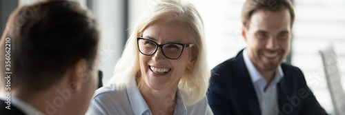 Mature businesswoman lead negotiations, during business meeting with company investor or client businesspeople laughing enjoy friendly talk concept Billede på lærred