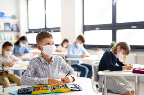 Leinwand Poster Children with face mask back at school after covid-19 quarantine and lockdown