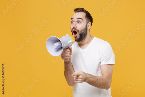 Fototapety, obrazy: Shocked young bearded man guy in white casual t-shirt posing isolated on yellow background studio portrait. People lifestyle concept. Mock up copy space. Scream in megaphone point index finger aside.