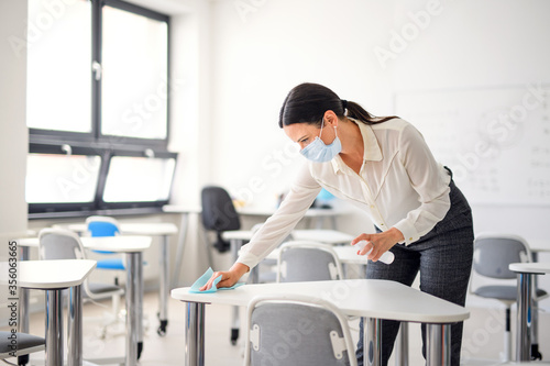 Teacher back at school after covid-19 quarantine and lockdown, disinfecting desks Canvas Print