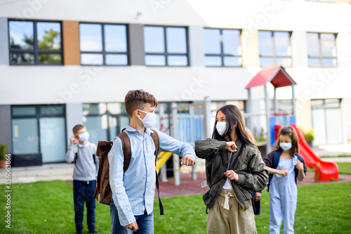 Foto Children with face mask going back to school after covid-19 lockdown, greeting