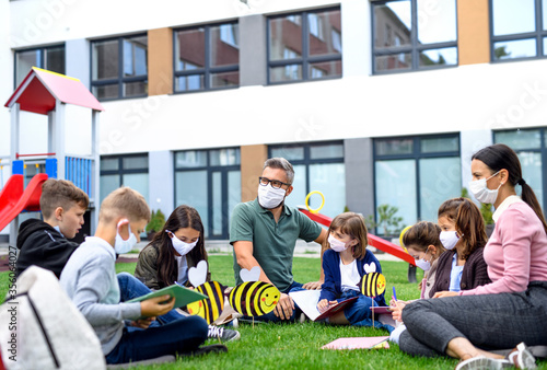 Group of cheerful children learning outdoors at school after covid-19 quarantine and lockdown Fototapete