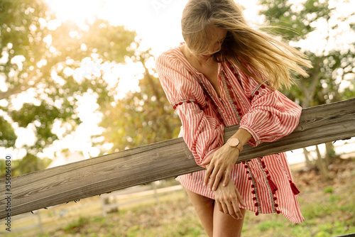 Fotografija Beautiful bohemian woman with windswept hair leaning on rustic fence