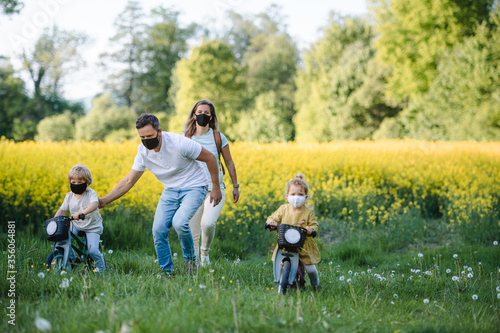 Fototapeta Family with two small children and face masks on cycling trip in countryside. obraz
