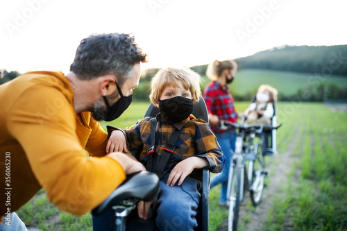 Fototapeta Family with two small children on cycling trip, wearing face masks. obraz
