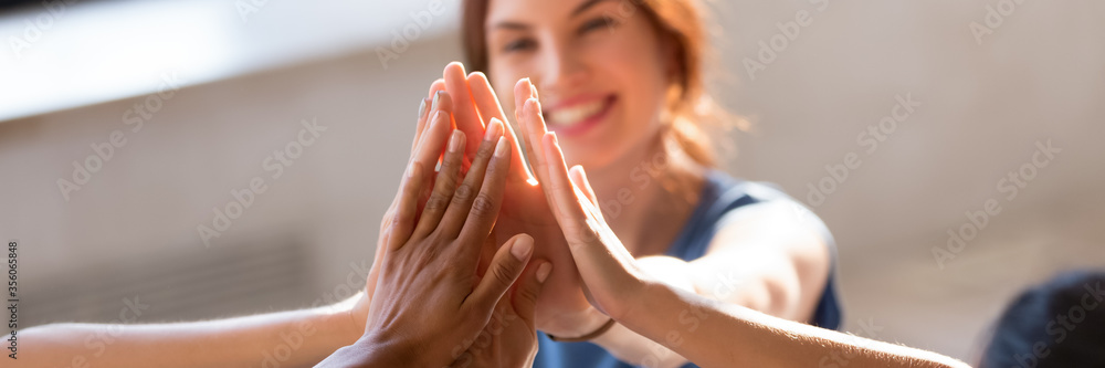 Fototapeta Horizontal photo banner for website header design, group of diverse young people giving high five feels excited close up focus on stacked palms. Respect and trust, celebration and friendship concept