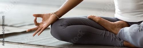 African woman wearing active wear do yoga practice meditating indoors, close up cropped photo lotus position Fototapet