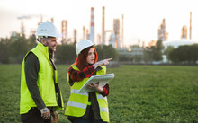 Two Young Engineers Standing Outdoors By Oil Refinery, Discussing Issues.