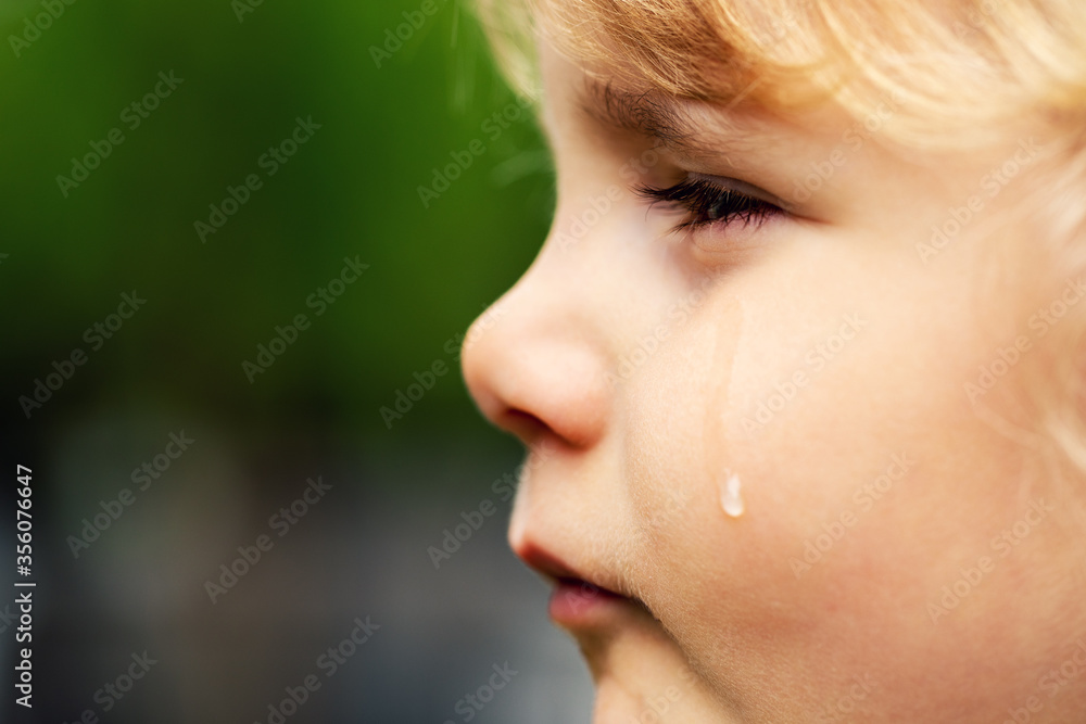 Fototapeta crying sad child - little girl face with tear on the cheek. concept of child rights and abuse