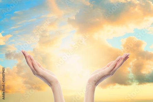 Woman hands reach for the sky clouds in prayer