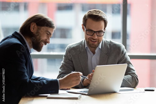 Fototapeta Caucasian teammates two positive businessmen sitting at desk in modern office looking at computer screen using learn new corporate e-business application, modern technology business management concept obraz na płótnie