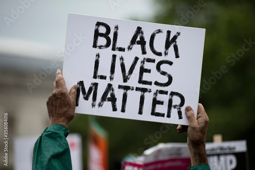 Cuadros en Lienzo A person holding a black lives matter banner at a protest