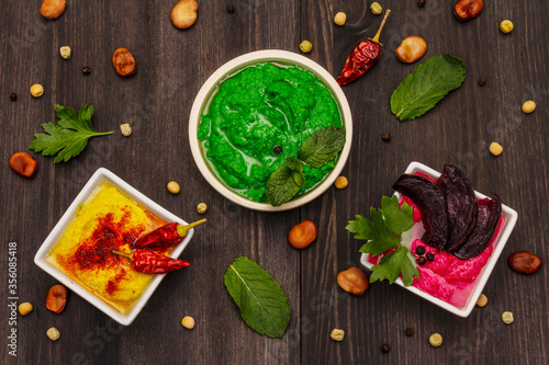 Fototapety, obrazy: Hummus, healthy vegan (vegetarian) food. Assorted three types: classic, mint and beetroot. Edamame dry beans, spices, fresh leaves