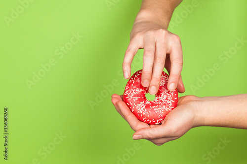 Female hands and a donut on a green background as a symbol of masturbation and foreplay (prelude) before sex. Touch the clitoris, erotic concept.