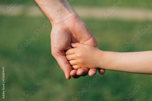 Fotografia Parent holding the hand of a small child