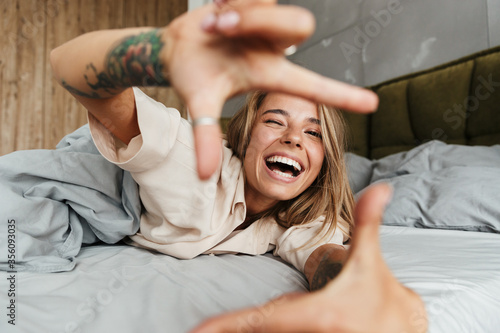 Obraz Image of woman making photo frame sign with fingers while lying in bed - fototapety do salonu